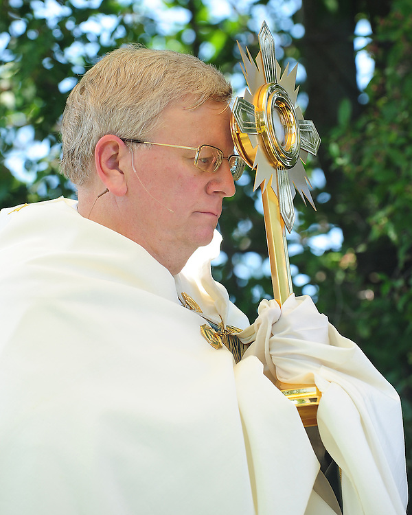Bishop David Ricken carries a monstrance holding the Blessed Sacrament during an outdoor rosary procession around the grounds of the Shrine of Our Lady of Good Help in Champion. The procession took place following an outdoor Mass celebrated on the feast of the Assumption of the Blessed Virgin Mary, Aug. 15. (Sam Lucero | The Compass)
