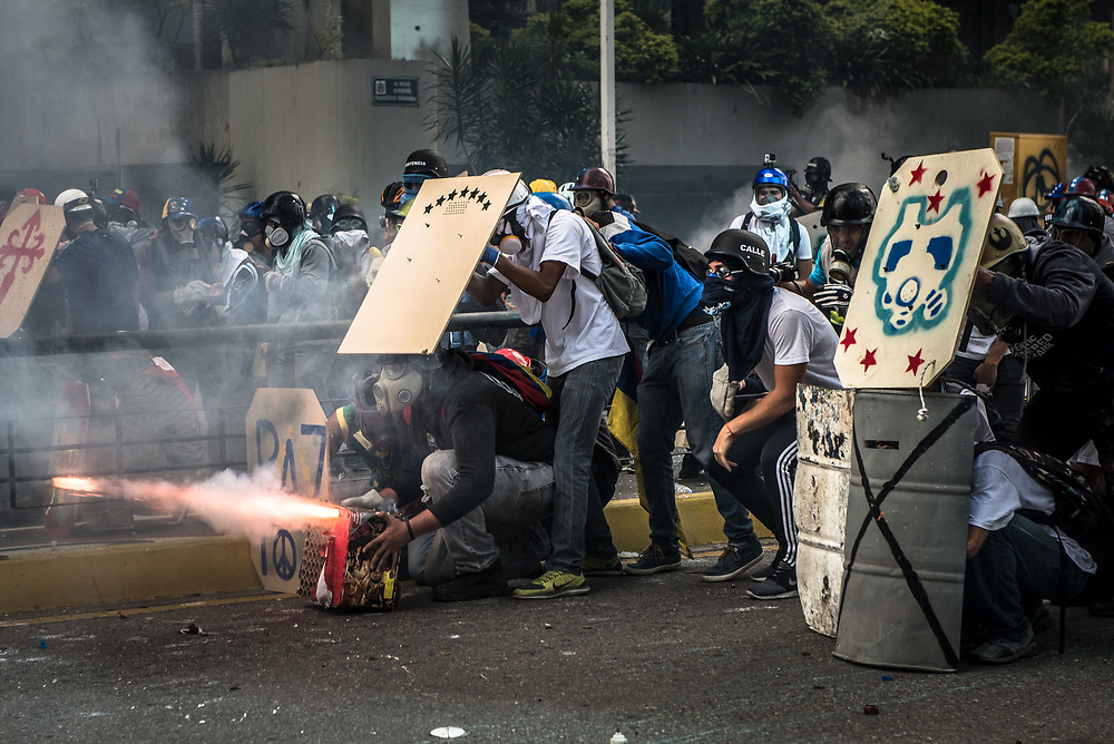 "CARACAS, VENEZUELA - MAY 20, 2017:  Anti-government protesters fire small firework rockets from what they call a ""torta"" (a big box of fireworks) at National the National Police who responded by heavily tear gassing and firing rubber bullets and buckshot at them. The streets of Caracas and other cities across Venezuela have been filled with tens of thousands of demonstrators for nearly 100 days of massive protests, held since April 1st. Protesters are enraged at the government for becoming an increasingly repressive, authoritarian regime that has delayed elections, used armed government loyalist to threaten dissidents, called for the Constitution to be re-written to favor them, jailed and tortured protesters and members of the political opposition, and whose corruption and failed economic policy has caused the current economic crisis that has led to widespread food and medicine shortages across the country.  Independent local media report nearly 100 people have been killed during protests and protest-related riots and looting.  The government currently only officially reports 75 deaths.  Over 2,000 people have been injured, and over 3,000 protesters have been detained by authorities.  PHOTO: Meridith Kohut"