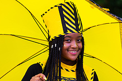 A young woman smiles for the camera as day one, Children's Day, of the Notting Hill Carnival gets underway in London. London, August 25 2019.