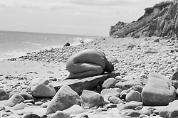 Nude woman distorting her body on a rock in Montauk, NY