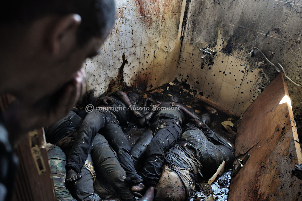 Gaza Strip, Kuzah'a:  A man holds his breath as he looks at five Palestinian dead bodies massed in the bathroom of a house in the bordering village of Kuzah'a on 1 August, 2014. ALESSIO ROMENZI