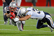 New England running back Kevin Faulk dives through the tackle of San Diego's Eric Weddle for a first down in the fourth quarter.