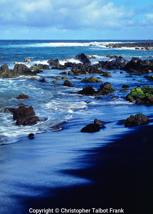 One of the cool features of a volcanic island that I like to photograph is the black sand beach like this one on Hawaii.  This stark photo has the deep blue Pacific Ocean water coming ashore on a pure black sandy beach.