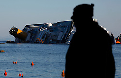 A man walks along the beach near the Costa Concordia cruise ship which ran aground off the west coast of Italy at Giglio island January 26, 2012. <br /> REUTERS/Darrin Zammit Lupi (ITALY)