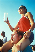 A girl on a man's shoulders in the crowd watching a gig, Glastonbury Festival, UK 1999