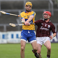 Clare's Martin Duggan gets his strike away under pressure from Galway's Kevin Brady in the All Ireland Intermediate Semi Final. - Photograph by Flann Howard