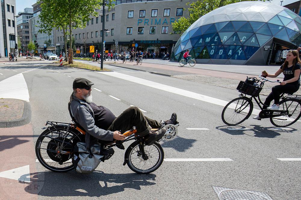 In Eindhoven fietst een man op een Nazca ligfiets door de binnenstad.<br /> <br /> In Eindhoven an man rides a recumbent bike at the city center.