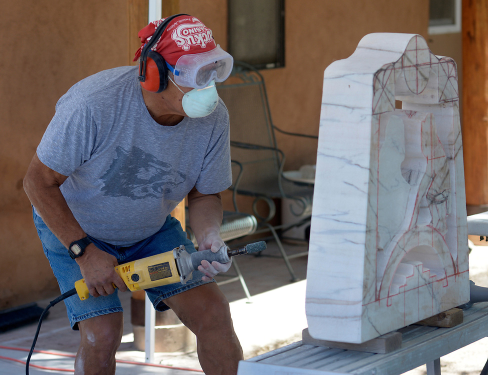 gbs061317j/ARTS -- Upton Ethelbah, Jr. checks his work as he uses a die grinder to sculpt Santa Clara Pueblo ram dancers out of Portuguese marble at his studio on Tuesday, June 13, 2017. (Greg Sorber/Albuquerque Journal)
