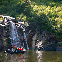 Guests on an inflatable zodiac boat ride come close to a waterfall in Rudyerd Bay in the Misty Fjords National Monument, Alaska.