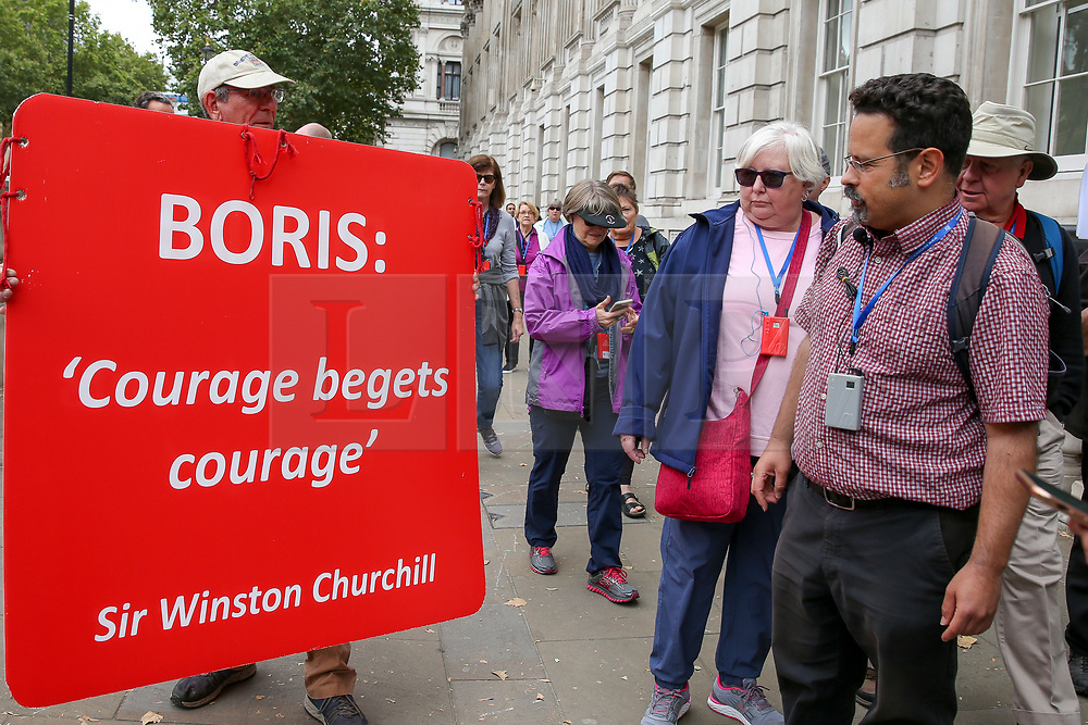 © Licensed to London News Pictures. 03/009/2019. London, UK. Tourists look at a Pro-Brexit supporter's poster outside Cabinet Office. MPs return to Westminster for a no deal  showdown that could result in a snap election. Photo credit: Dinendra Haria/LNP