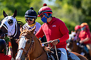 HOT SPRINGS, AR - MAY 02:  Outrider leads a horse while wearing a mask for protection during the Covid-19 Pandemic on Derby Day at Oaklawn Racing Casino Resort on May 2, 2020 in Hot Springs, Arkansas. (Photo by Wesley Hitt/Getty Images)