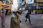 An older Japanese man uses an old style flip cellphone in a street in Shinjuku, Tokyo, Japan Friday February 23rd 2018