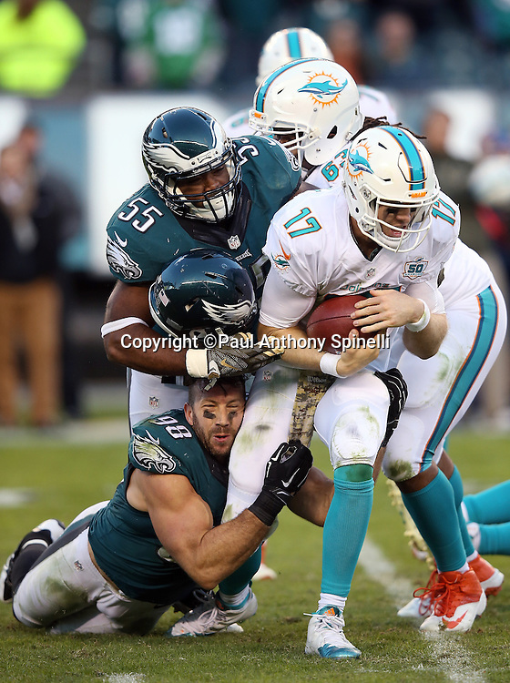 Philadelphia Eagles outside linebacker Connor Barwin (98) loses his helmet as he sacks Miami Dolphins quarterback Ryan Tannehill (17) on third down, with help from Philadelphia Eagles outside linebacker Brandon Graham (55), forcing a punt on the next play that gives the Eagles one last offensive series with less than two minutes left in the fourth quarter during the 2015 week 10 regular season NFL football game against the Miami Dolphins on Sunday, Nov. 15, 2015 in Philadelphia. The Dolphins won the game 20-19. (©Paul Anthony Spinelli)