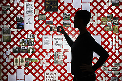 April 27, 2018 - Wakefield, Yorkshire, UK - Wakefield UK. A visitor takes a photograph on her phone of the latticework wall of photos & words by Alec Finlay at the Yorkshire Sculpture Park this morning. The art work features in a new exhibition at the park which showcases the radical & vital work of arts & environment charity Common Ground. (Credit Image: © Andrew Mccaren/London News Pictures via ZUMA Wire)