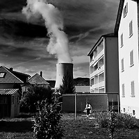 Girl playing in a village close to Gösgen Nuclear Power Plant (Kernkraftwerk Gösgen), with a plume of smoke from its cooling tower rising behind.  Nucleur power, from four plants, provides 40% of the country's electricity needs.