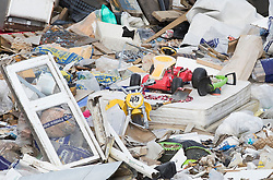 © Licensed to London News Pictures. 29/03/2018. London, UK. A window, mattress and children's toys are amongst a large pile of waste and rubbish which has been dumped in an area of scrap land next to houses and a recreation park in Edmonton, north London. Local residents are calling it a 'river of rubbish' and say it has been there for a month and are campaigning for it's removal.  Photo credit: Peter Macdiarmid/LNP