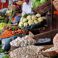 Vendor at Vegetable Stand at Street Market in Mumbai, India<br /> This vegetable vendor at a street market in Mumbai, India, looks relaxed, but if you take one look at his garlic bulbs, cloves, carrots, cauliflower or cabbage, he will spring into action and grab a plastic bag in anticipation of selling you something.