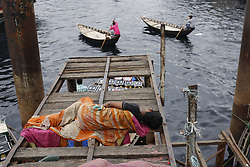 April 28, 2018 - Dhaka, Bangladesh - A homeless boy sleeps on a bridge as boatmen run for passenger for in the Shore of Buriganga River. (Credit Image: © Md. Mehedi Hasan via ZUMA Wire)