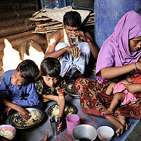 A family of a rickshaw puller having lunch in Korail Slum. Korail is the largest slum in Dhaka, Bangladesh.<br /> <br /> Rickshaw is the most important transport of Bangladesh. The rickshaw driver comes from the lower level in Bangladesh society. Almost Rickshaw puller comes from the village of Bangladesh since there no enough job opportunities due to various factors.