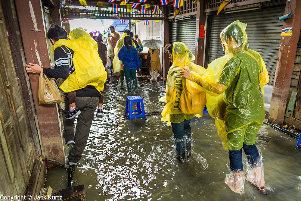 23 SEPTEMBER 2013 - BANGKOK, THAILAND: Tourists walk out of the flooded Tha Tien Pier on the Chao Phraya River in Bangkok. More than a quarter of the provinces in Thailand are reporting some flooding as heavy rainy season storms continue in central Thailand. Rain is expected to continue through this week, raising the possibility of serious flooding throughout the country. More than 600,000 Thais have been impacted by the flooding so far this year. Flooding in 2011 killed more than 800 people and cut economic growth for the year to just .10 percent.     PHOTO BY JACK KURTZ