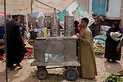 A chai (tea) seller walks through the weekly market at Qurna, a village on the West Bank of Luxor, Nile Valley, Egypt.