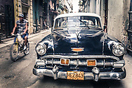 Havana Street Photography - man riding bicycle past antique car