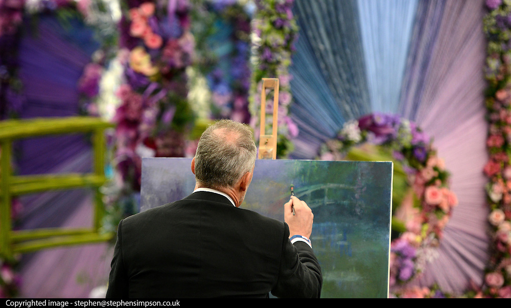 © Licensed to London News Pictures. 21/05/2012. Chelsea, UK. A man paints one of the exhibits, a homage to Monet's garden in Paris. Press preview of The Chelsea Flower Show today 21 May 2012. The world's most famous flower show, which has been held in the grounds of the Royal Chelsea Hospital since 1913, will be open to the public from Tuesday. Visitors are expected to flock in their thousands to see displays of plants, flowers and furniture for ideas on how to decorate their gardens.. Photo credit : Stephen Simpson/LNP