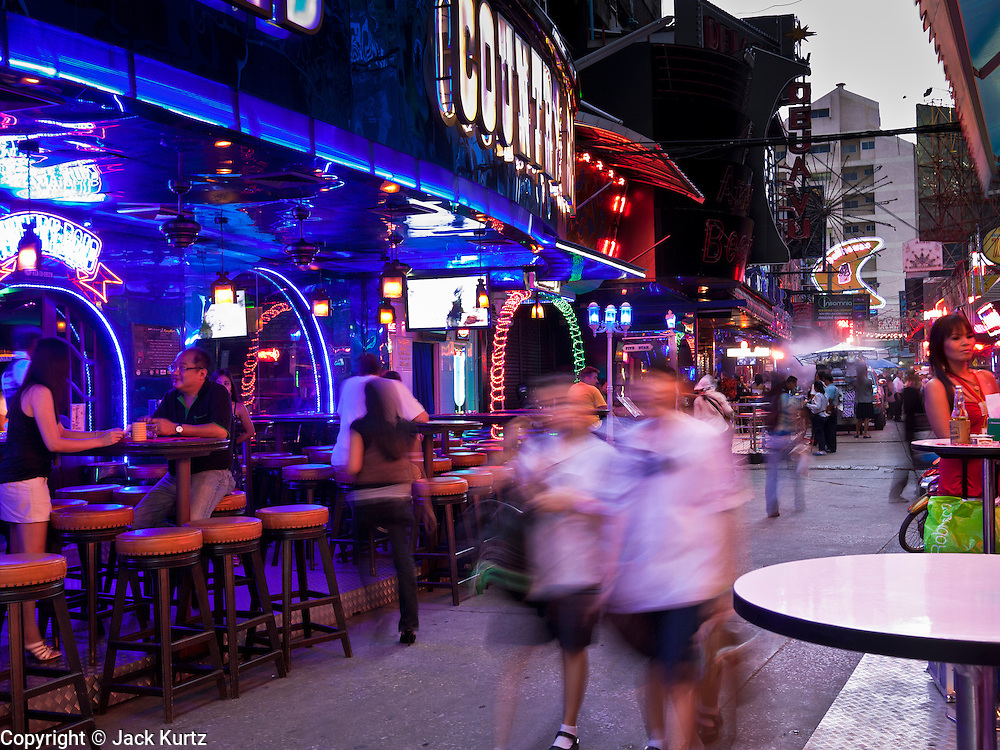 """12 JULY 2011 - BANGKOK, THAILAND:  Schoolgirls walk down Soi Cowboy, a """"red light"""" district in Bangkok after school. Prostitution in Thailand is illegal, although in practice it is tolerated and partly regulated. Prostitution is practiced openly throughout the country. The number of prostitutes is difficult to determine, estimates vary widely. Since the Vietnam War, Thailand has gained international notoriety among travelers from many countries as a sex tourism destination. One estimate published in 2003 placed the trade at US$ 4.3 billion per year or about three percent of the Thai economy. It has been suggested that at least 10% of tourist dollars may be spent on the sex trade. According to a 2001 report by the World Health Organisation: """"There are between 150,000 and 200,000 sex workers (in Thailand).""""  PHOTO BY JACK KURTZ"""