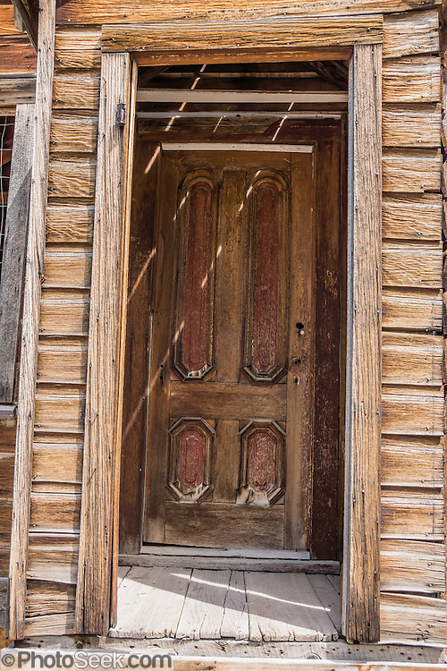 "A dilapidated wood door ages at Bodie, California's official state gold rush ghost town. Bodie State Historic Park lies in the Bodie Hills east of the Sierra Nevada mountain range in Mono County, near Bridgeport, California, USA. After W. S. Bodey's original gold discovery in 1859, profitable gold ore discoveries in 1876 and 1878 transformed ""Bodie"" from an isolated mining camp to a Wild West boomtown. By 1879, Bodie had a population of 5000-7000 people with 2000 buildings. At its peak, 65 saloons lined Main Street, which was a mile long. Bodie declined rapidly 1912-1917 and the last mine closed in 1942. Bodie became a National Historic Landmark in 1961 and Bodie State Historic Park in 1962."