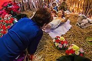 24 DECEMBER 2013 - BANGKOK, THAILAND: A woman kisses the feet of a doll that represents the Baby Jesus in a nativity scene during Christmas services at Holy Redeemer Church in Bangkok. Thailand is predominantly Buddhist but Christmas is widely celebrated throughout the country. Buddhists mark the day with secular gift giving but there are about 300,000 Catholics in Thailand who celebrate religious Christmas. Catholics first came to Thailand (then Siam) in 1567 as chaplain for Portuguese mercenaries in the employ of the Siamese monarchy. There has been a continuous Catholic presence in Thailand since then.   PHOTO BY JACK KURTZ