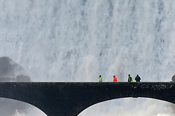 © Licensed to London News Pictures. 11/02/2019. Elan Valley, Powys, Wales, UK. Workmen walk across a bridge as water cascades over the Caban-coch dam, at Elan Valley village near Rhayader in Powys, Wales, UK after recent torrential rain in Powys has filled the complex of Elan valley dams and taken river levels to the tops of river banks in Powys, Wales, UK. Elan Valley dams supply Birmingham in the West Midlands UK with water via a gravity feed. credit: Graham M. Lawrence/LNP