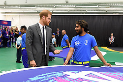 The Duke of Sussex speaks to a flag bearer as he attends the opening match of the 2019 ICC Cricket World Cup between England and South Africa at The Oval in London.