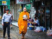 25 AUGUST 2016 - BANGKOK, THAILAND: A monk on his morning alms rounds walks past the flower market in Bangkok. Most Thai males enter the monastery and become monks or novices (young monks) at some point in their lives.         PHOTO BY JACK KURTZ