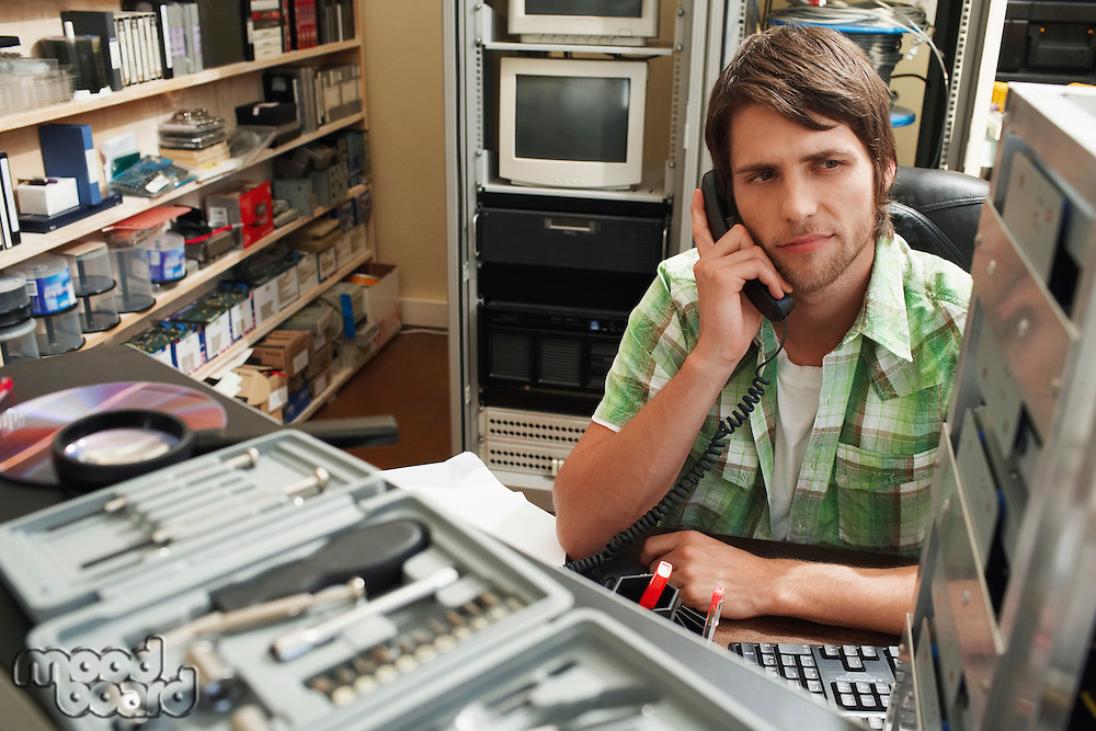 Man using phone surrounded by computer equipment.