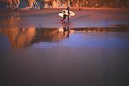 Two surfers in the beach at sunset. Sopelana, Bizkaia