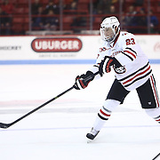 Colton Saucerman #23 of the Northeastern Huskies passes the puck during the game at Matthews Arena on January 18, 2014 in Boston, Massachusetts. (Photo by Elan Kawesch)