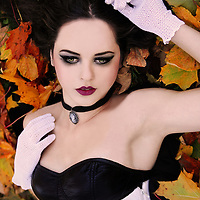 A close-up of a pretty girl with pale skin, black hair and heavy make-up lying in fallen autumn leaves.