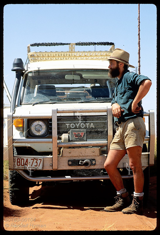 Field assistant Dave Wurst leans on Land Cruiser and surveys mala reintro site in Tanami Desert. Australia