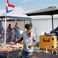 Nederland, Amsterdam , 27 juli 2014.<br /> het Kwaku-festival, in het Bijlmerpark in Amsterdam-Zuidoost.<br /> Dat festival is jarenlang het toneel geweest van gedoe, met betrokkenen binnen de organisatie die elkaar de tent uitvochten en zo. Maar sinds vorig jaar , sinds er een nieuwe organisatie achter zit, loopt het goed.<br /> &eacute;&eacute;n stand, die van Wan2Connect, een netwerk van etnisch ondernemers dat beginnende allochtonen ondernemers op weg wil helpen. De gedachte is dat beginnende allochtone ondernemers veel vaker failliet gaan dan autochtone, omdat ze bepaalde vaardigheden missen. Dit netwerk wil hen daarbij helpen, en wil op Kwaku zichzelf presenteren, onder meer door bezoekers een soort &lsquo;ondernemerstest&rsquo; af te nemen.<br /> Op de foto: 2 vertegenwoordigers van de Wan2connect stand in gesprek met allochtone ondernemers van een sparerib stand.<br /> Foto:Jean-Pierre Jans