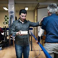Nederland. Geleen. 9 april 2015.<br /> De uit Syrie afkomstige Mahmoud Ibraim is als vrijwilliger werkzaam bij een vestiging van Orbis.<br /> In syrie was Mahmoud fysiotherapeut. <br /> Op de foto meet hij de bloeddruk en hartslag  van een client in de fysioruimte van Orbis Glana aan de Lienaertstraat.