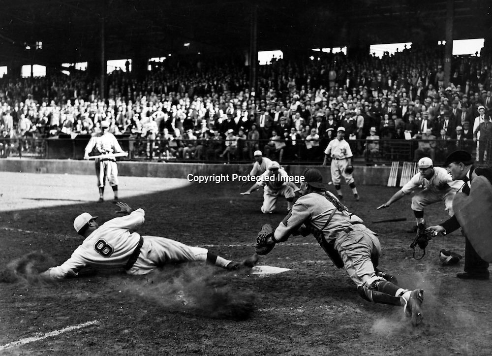 Apr. 10, 1938: Frenchy Uhalt, Hollywood Stars outfielder, had plenty of moral support as he slid across plate in ninth inning with run that beat the San Francisco Seals, 4-3, in the double hitter opener at Wrigley Field. Uhalt scored from second on Tom Carey's single, barely beating Holder's throw to catcher Woodall, shown diving as Frenchy's toe flicks a corner of the plate. The umpire is Henry Fanning. Photo won HM in Sports in the 1939 Los Angeles Press Photograpahers annual contest. Jack Herod/Los Angeles Times/From the Archive