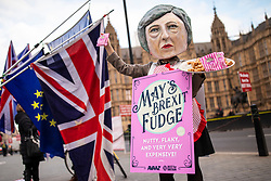 "© Licensed to London News Pictures. 10/12/2018. London, UK. A protester from the campaign group Avaaz wears a Theresa May mask and hands out ""Brexit Fudge"" as MPs continue to debate the Prime Minister's proposed Brexit deal. Photo credit: Rob Pinney/LNP"