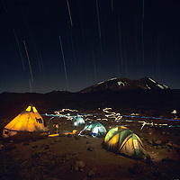 Africa, Tanzania, Kilimanjaro National Park, Climbing party's tents glowing at night under starry sky on rocky plateau at Shira 2 Camp (12800') on Mount Kilimanjaro climbing expedition