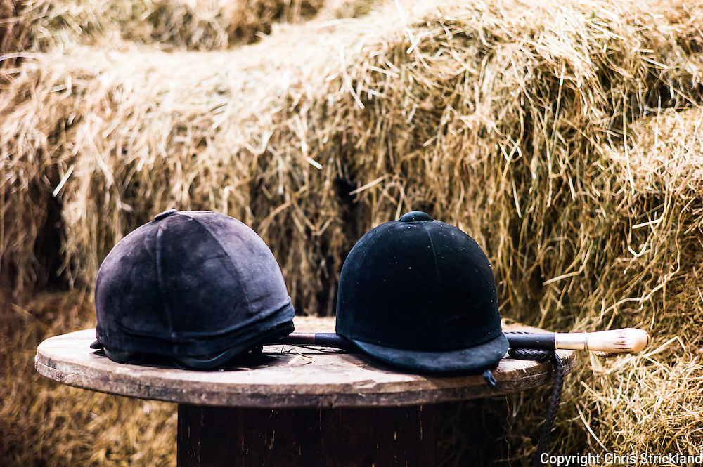 Jedburgh, Scottish Borders, UK. 18th February 2016. Riding hats and a hunting crop rest on a table in a hay barn.