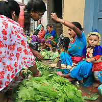 A mother and child work side-by-side at a street market in Kathmandu, Nepal, Oct. 6, 2009.