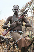 Africa, Ethiopia, Debub Omo Zone, Mursi tribesmen. A nomadic cattle herder ethnic group located in Southern Ethiopia, close to the Sudanese border. A warrior with a AK-47 rifle