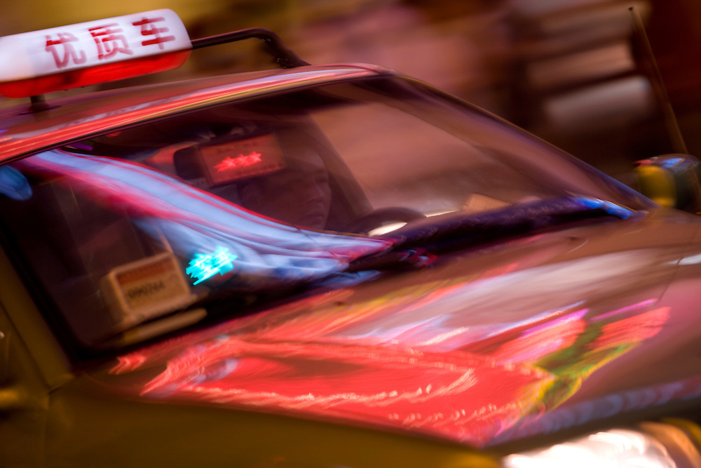 Asia, China, Shanghai, Blurred image of taxi cab driving at night along neon-lit crowded Nanjing Road, a shopping district lined with western and Chinese retail stores and restaurants.
