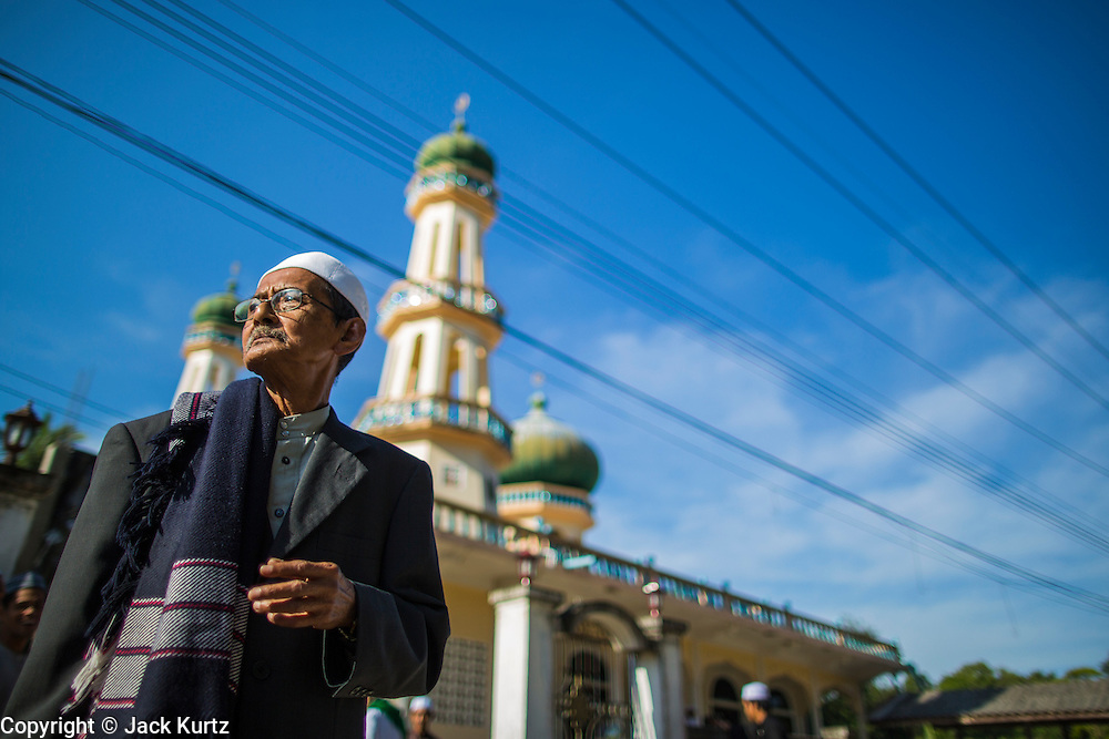 26 OCTOBER 2012 - PULASAIZ, NARATHIWAT, THAILAND:  Men leave the mosque after Eid al-Adha services in the villiage Pulasaiz, in the province of Narathiwat, Thailand. Eid al-Adha, also called Feast of the Sacrifice, is an important religious holiday celebrated by Muslims worldwide to honor the willingness of the prophet Ibrahim (Abraham) to sacrifice his firstborn son Ishmael as an act of submission to God, and his son's acceptance of the sacrifice before God intervened to provide Abraham with a ram to sacrifice instead. In 2012 Eid al-Adha was celebrated Oct 25 - 26.    PHOTO BY JACK KURTZ