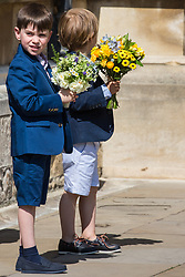 Windsor, UK. 21st April 2019. Local schoolchildren wait to give traditional posies of flowers to the Queen as she leaves the Easter Sunday service at St George's Chapel in Windsor Castle.