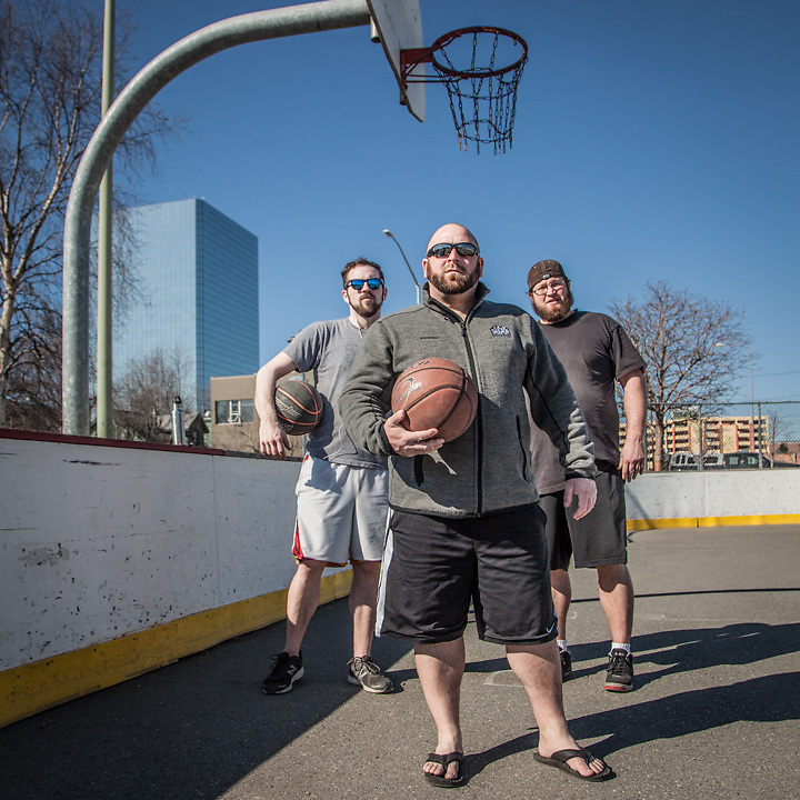 "Mark Hoffman (left), Greg Conners (center), and J.C. Durate (right) at the Delaney hockey rink and basketball court, Anchorage  ""We all met while working at the Glacier Brew House…we're all still in the hospitality business""  hoffsox@yahoo.com"